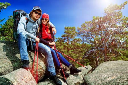 Couple of tourists are sitting at the top of a mountain with a feeling of freedom. photo