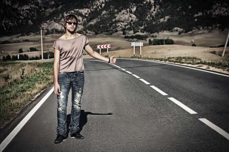 Handsome young man hitchhiker standing on a road over picturesque landscape. photo