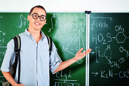 Young man student standing at the blackboard in the classroom. Stock Photo - 18086883