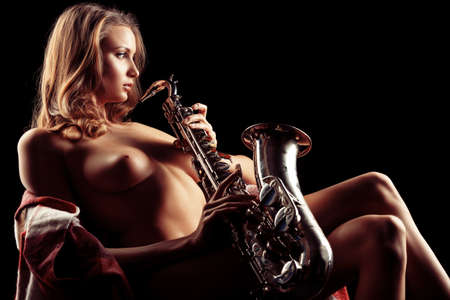 black girl nude: Art portrait of a beautiful naked woman with saxophone.