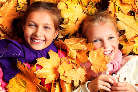 Portrait of two cute girls sisters lying on the leaves at the autumn park. photo