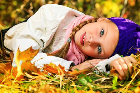 Portrait of a happy little girl lying on the leaves at the autumn park. photo