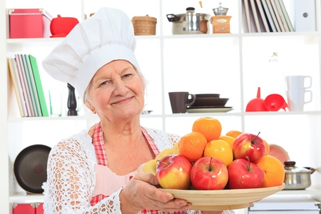 Senior woman chef cook standing with a plate of fruits in the kitchen. photo