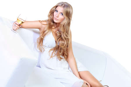 Beautiful blonde woman in light white dress sitting on a sofa. Isolated over white. photo