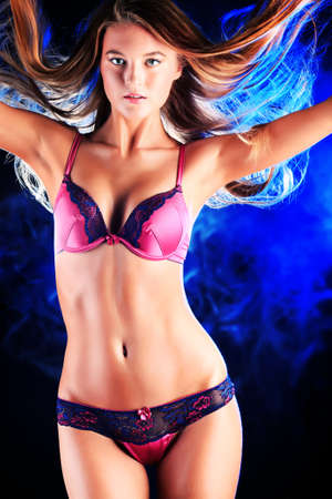 woman bra: Portrait of a sexual woman in lingerie over dark background with blue light.