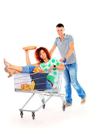 woman shopping cart: Cheerful couple with a shopping trolley. Isolated over white background.