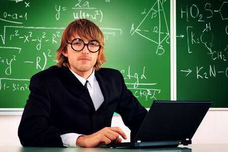 Portrait of a smart male student in a suit working on a laptop at a classroom. Stock Photo - 18207144