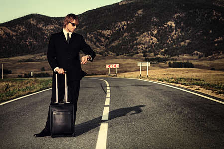 Handsome business man standing on a highway with his suitcase and looking at his watch. photo