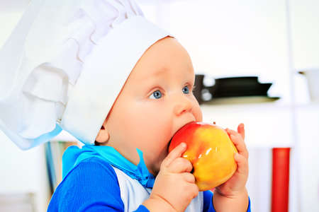 eating in: Cute small baby in the cook costume eating fresh apple at the kitchen. Stock Photo