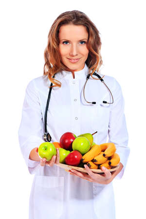 Portrait of a smiling woman doctor holding fresh fruits. Isolated over white background. photo