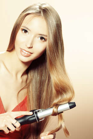 curling irons: Beautiful young woman doing hairstyle with curling irons.