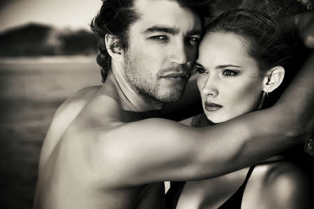 male fashion model: Black-and-white portrait of a sexual young couple in love having holidays on the sea.
