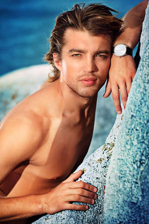 wristwatch: Portrait of a handsome male model posing at the seaside.