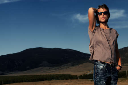 young man jeans: Handsome young man posing over picturesque landscape. Stock Photo