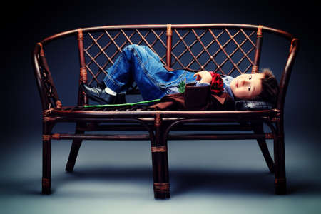 Cute little boy lying on a bench. Vintage style. Stock Photo - 18352806