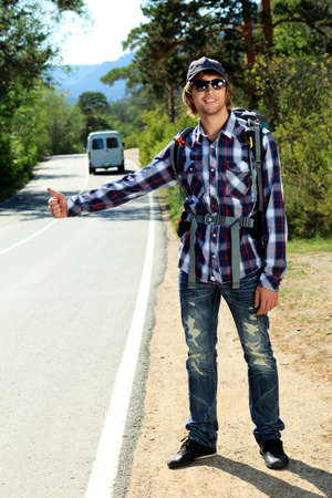 Young man tourist hitchhiking along a road. photo