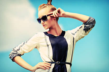 Fashion woman posing over blue sky.