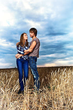 Romantic young couple in casual clothes standing together in a wheat field on a background of the storm sky.  photo