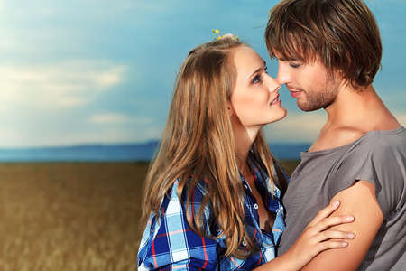 two sexy women: Romantic young couple in casual clothes standing together in a wheat field on a background of the storm sky.