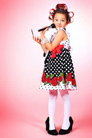 Retrato de un lindo poco pin-up girl sobre fondo rosa.