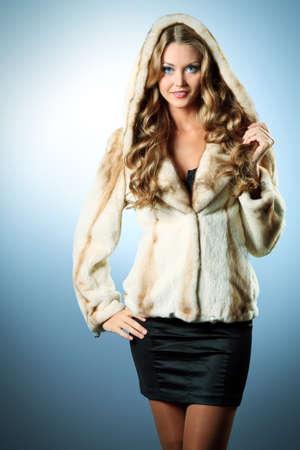 woman in fur coat: Beautiful glamorous woman in fur coat posing at studio.