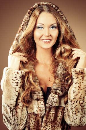 Beautiful glamorous woman in fur coat posing at studio. photo