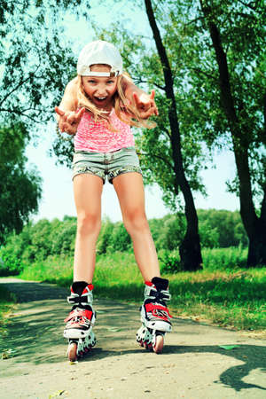 roller skates: Cute girl in roller skates at a summer park. Stock Photo
