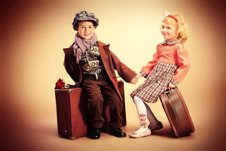 Cute little boy is sitting on the old suitcase with charming little lady. Retro style. photo