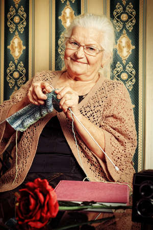 Portrait of a smiling senior woman knitting on spokes at home. Old-fashioned style. photo