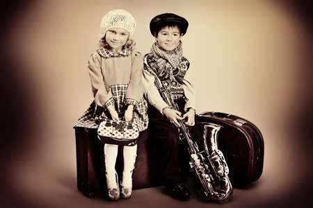 Cute little boy with his old saxophone is sitting on a suitcase with charming little lady. Retro style. photo