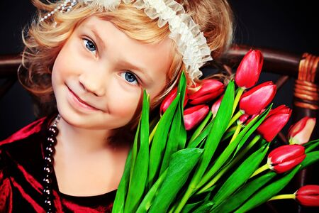 Portrait of a charming little lady with a bouquet of tulips sitting on a bench. Vintage style. Stock Photo - 18520291