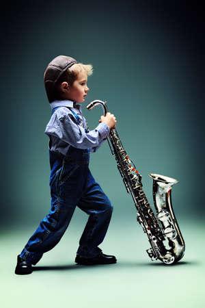 saxofon: Retrato de un niño pequeño lindo músico de jazz tocando su saxofón. Estilo retro.