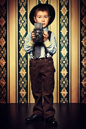 film shooting: Little boy looking like a gentleman standing with a camera. Vintage background.