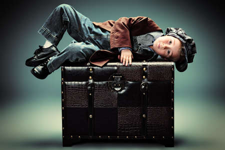 Portrait of a cute little boy lying on a huge old trunk. Vintage style. Stock Photo - 18547719