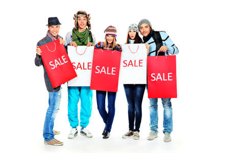 Group of cheerful young people with shopping bags. Isolated over white background. photo
