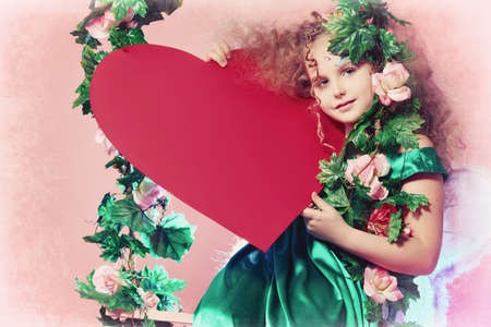 Beautiful little fairy holding red heart over pink background. photo