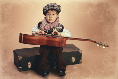 Portrait of a romantic little boy sitting with his guitar. Retro style. Standard-Bild
