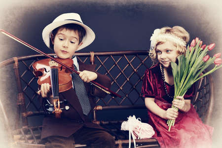 vintage children: Cute little boy is playing the violin to the charming little lady. Retro style. Stock Photo