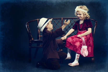 Cute little boy admitted in love the charming little lady. Retro style. photo