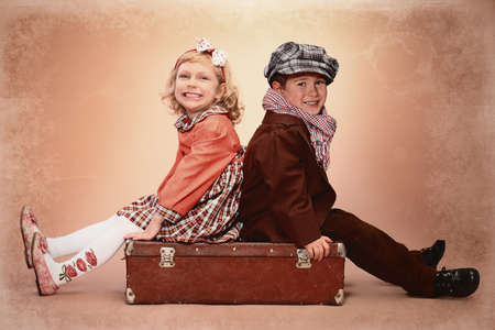 boy lady: Cute little boy is sitting on the old suitcase with charming little lady. Retro style. Stock Photo