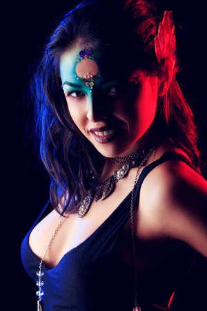 maquillaje de fantasia: Retrato de una mujer joven y hermosa con maquillaje de fantasía. Fondo negro.