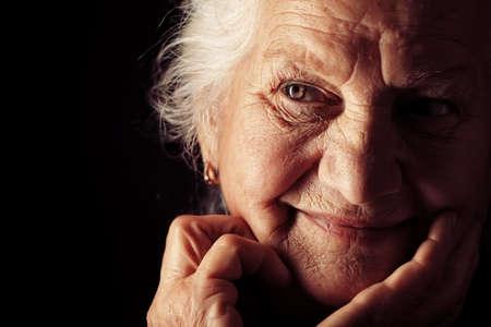カメラに向かって笑みを浮かべて満足している年配の女性の肖像画。黒背景。