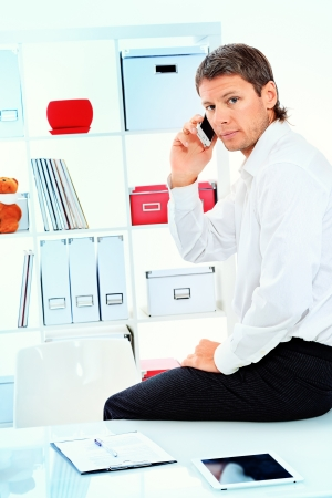 Handsome businessman is talking on a cell phone at the modern office. photo