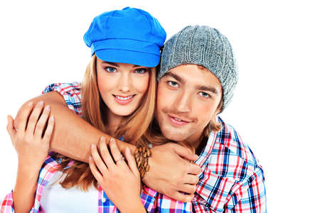 young couple smiling: Portrait of a happy young couple standing together over white background Stock Photo