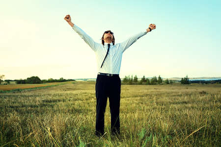 purposeful: Happy businessman standing in the field and enjoying success.