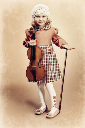 Portrait of a pretty little girl posing with her violin. Vintage style. photo