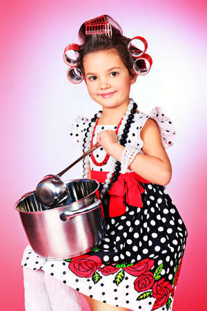 retro housewife: Portrait of a cute little pin-up girl with a pan over pink background.