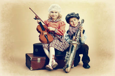 Cute little boy with his old saxophone is sitting on a suitcase with charming little lady violinist. Retro style. Stock Photo - 18682734