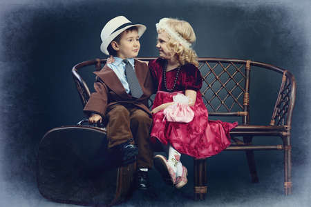Cute little boy with an old suitcase is sitting on a bench with charming little lady. Retro style. photo