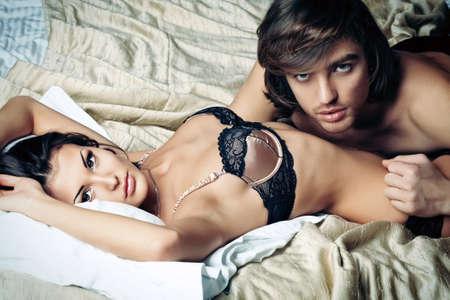 sexo pareja joven: Sexy joven pareja jugando en juegos de amor en un dormitorio. Foto de archivo